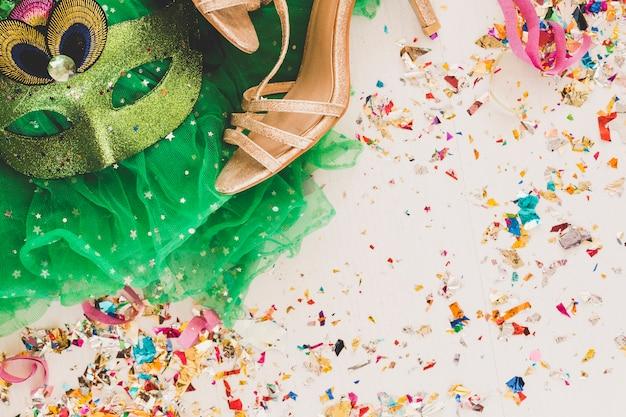 Máscara de festa e sapatos dourados em branco