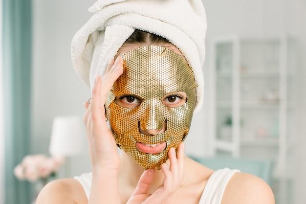 Máscara de folha de ouro de mulher. mulher jovem e bonita toalha branca na cabeça com cosméticos de pele dourada, olhando para a câmera. tratamento e tratamento de beleza