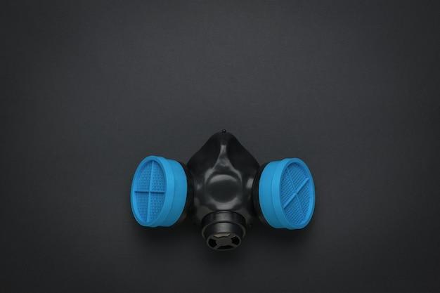 Máscara de gás com filtros azuis em uma superfície preta