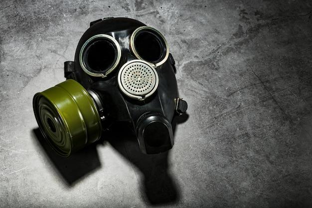Máscara de gás em um fundo de pedra preto com um filtro em caixa verde. conceito pós-apocalíptico.