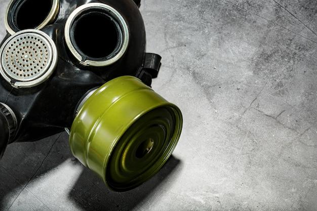 Máscara de gás em um fundo de pedra preto, proteção contra infecções perigosas.
