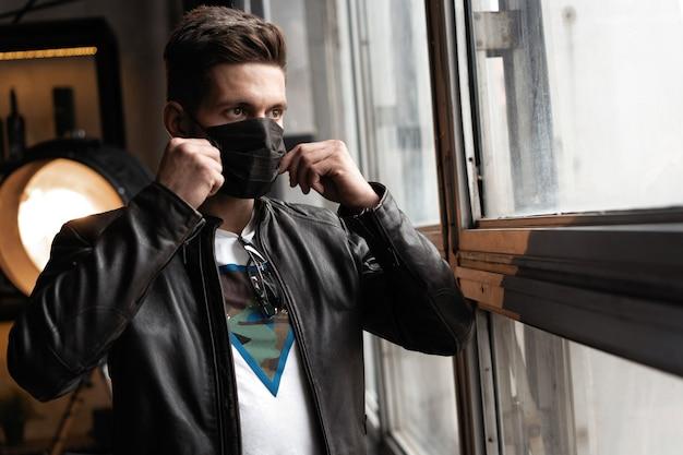 Máscara de jovem bonito preto. homem elegante com uma jaqueta de couro em pé e olhando para a janela