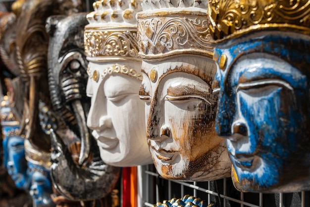 Máscara de madeira com a imagem do buda em exposição à venda no mercado de rua em ubud, bali, indonésia. vitrine de loja de artesanato e souvenirs, de perto