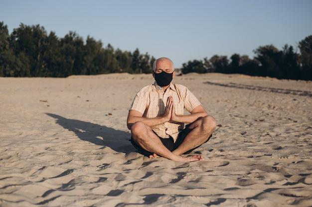 Máscara de medicina vestindo homem sênior em pose de lótus, sentado na areia. conceito de calma e meditação.