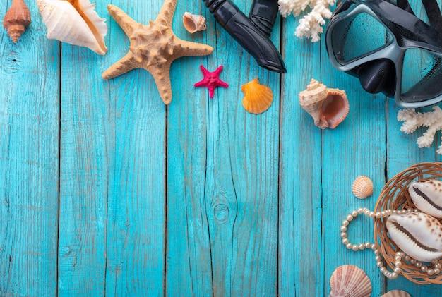 Máscara de mergulho com estrela do mar e conchas do mar em madeira azul velha. vista do topo. postura plana.