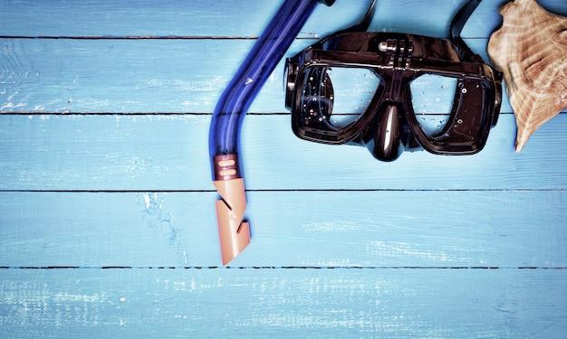 Máscara de mergulho e snorkel em um fundo azul de madeira