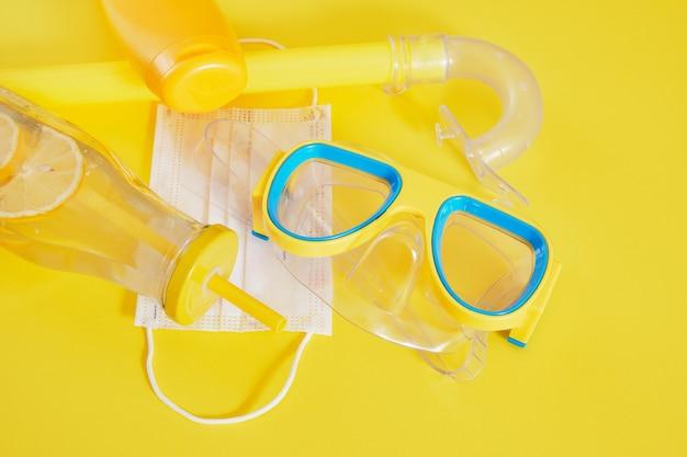 Máscara de mergulho, máscara médica protetora, filtro solar e garrafa de limonada, conceito de férias na praia em bloqueio