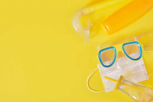 Máscara de mergulho, máscara médica protetora, filtro solar e garrafa de limonada em fundo amarelo, conceito de férias na praia em bloqueio