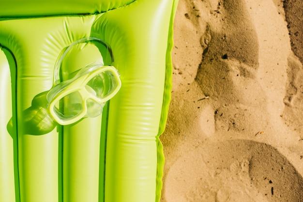 Máscara de mergulho no colchão na areia