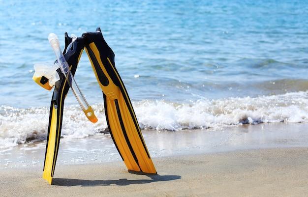 Máscara de mergulho, snorkel e nadadeiras em uma praia de areia tropical