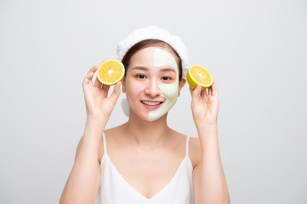 Máscara de mulher jovem muito asiática, hidratante e rejuvenescedor, descamação da pele limpa, segurando pedaços de laranja sobre fundo branco.