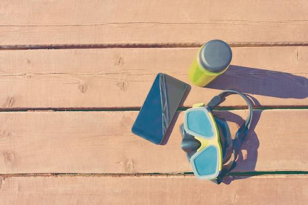 Máscara de natação, garrafa de suco e smartphone na mesa de madeira em dia ensolarado de férias