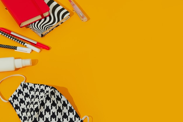 Máscara de papelaria e desinfetante para as mãos contra a mesa laranja