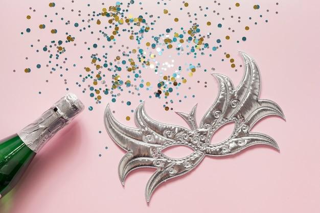 Máscara de prata com lantejoulas e garrafa de champanhe