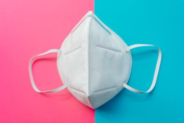Máscara de proteção antivírus padrão ffp2 para prevenir covid-19. fundo meio rosa e azul