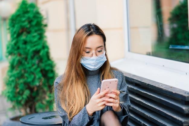 Máscara de proteção contra a propagação do vírus da gripe contra doenças e vírus da gripe. mulher asiática usando máscara cirúrgica no rosto em espaços públicos. cuidados de saúde.