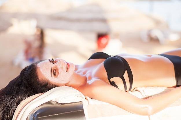 Máscara de spa, mulher bonita obter máscara de spa na praia ensolarada no salão spa ao ar livre
