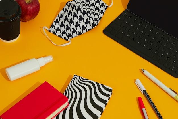 Máscara de teclado de papelaria e desinfetante para as mãos contra mesa laranja