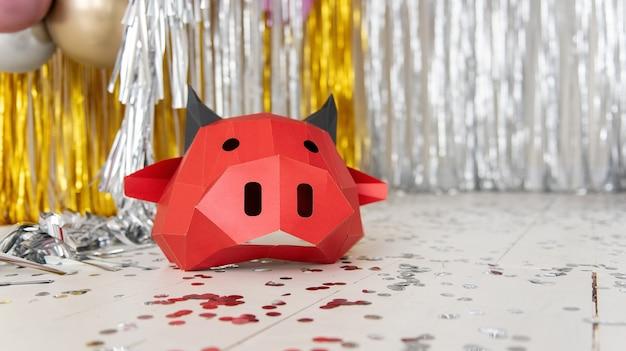 Máscara de touro de papelão vermelha deitada em um chão prateado