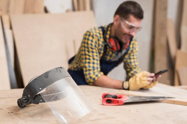 Máscara de vidro protetora e serrote na bancada e carpinteiro usando celular no fundo