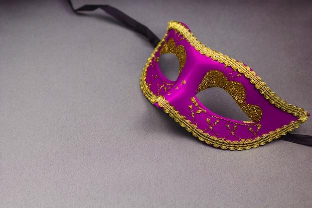 Máscara decorativa rosa sobre fundo cinzento, cópia espaço