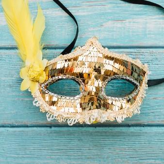 Máscara dourada com lantejoulas e pena