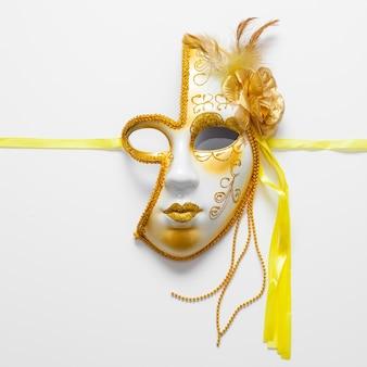Máscara dourada de close-up para carnaval e fitas amarelas