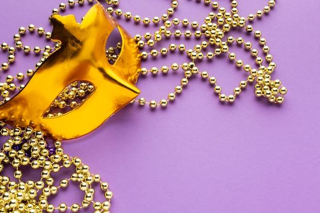 Máscara dourada e decorações de pérolas