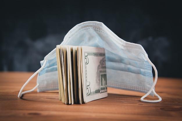 Máscara e notas de dólar na mesa