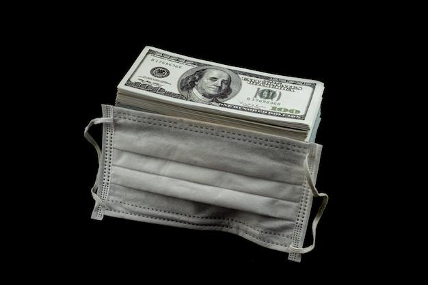 Máscara e proteção contra vírus e dinheiro uma pilha de 100 dólares americanos