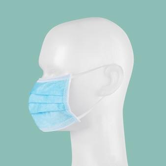 Máscara facial cirúrgica descartável azul em um manequim