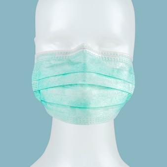 Máscara facial cirúrgica descartável verde em um manequim