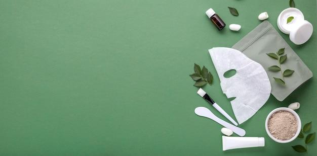 Máscara facial cosmética de tecido com conjunto de espátula e escova de máscara de argila cosmética, creme hidratante em tubo, frasco. tratamentos de spa de beleza para cuidados com a pele facial, cosmetologia long web banner copy space green. Foto Premium
