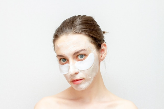 Máscara facial cosmética na linda garota. mulher jovem usa tapa-olhos.