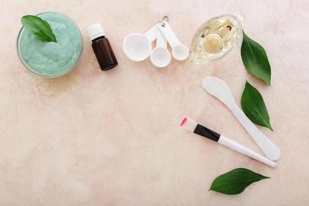 Máscara facial de abacate, espátula, pincel, colheres medidoras, óleo, óleo essencial sobre fundo rosa claro