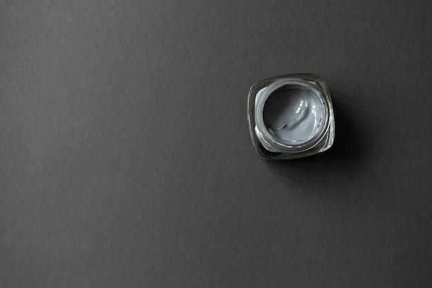 Máscara facial de argila de carvão vegetal em fundo preto com espaço de cópia, vista superior.