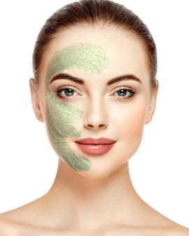 Máscara facial de argila de mulher descascando o retrato da beleza. tiro do estúdio. isolado no branco.
