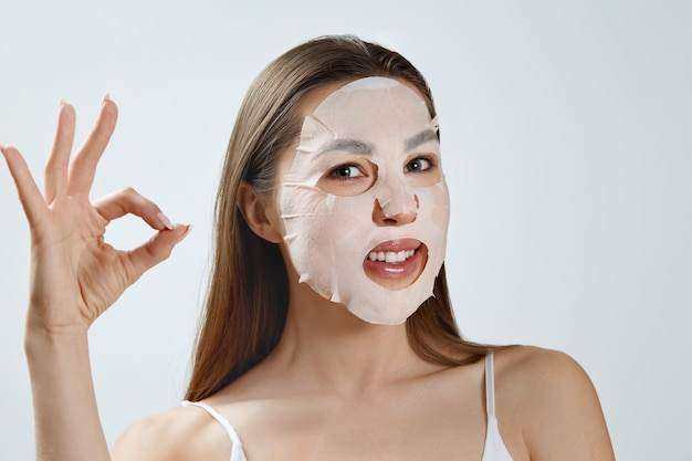 Máscara facial de beleza. mulher jovem e bonita com uma máscara hidratante de pano no rosto. cuidados com a pele. máscara cosmética de spa. tratamento facial