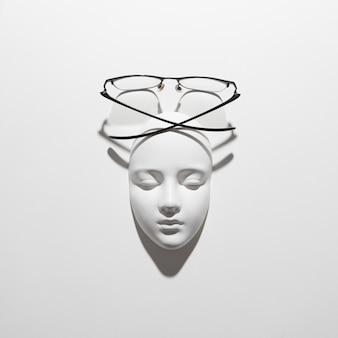 Máscara facial de gesso com óculos elegantes acima dela em uma parede branca com sombras suaves e longas, copie o espaço. postura plana. estilo de moda ótica.