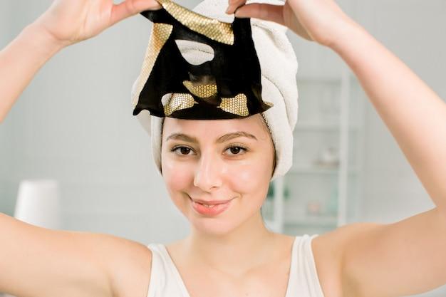 Máscara facial de mulher. closeup linda garota sorridente em toalha branca decolando folha cosmética máscara de ouro da pele saudável.