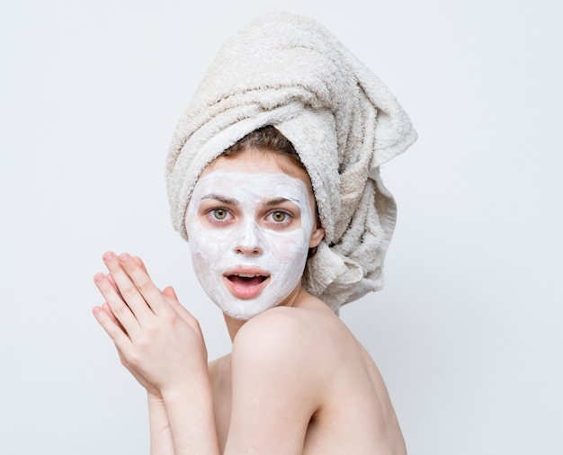 Máscara facial de mulher em creme, ombros nus, pele limpa