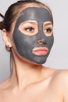 Máscara facial de mulher. retrato de menina bonita, removendo a máscara preta cosmética da pele do rosto. closeup de mulher jovem e atraente com maquiagem natural e máscara de peeling cosmético no rosto. alta resolução