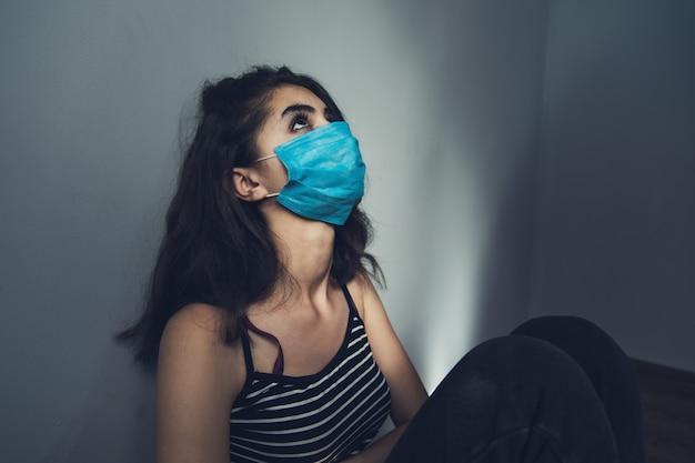 Máscara facial de mulher triste na sala
