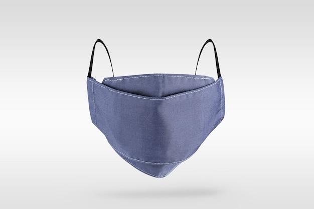 Máscara facial de tecido azul-púrpura claro em fundo cinza