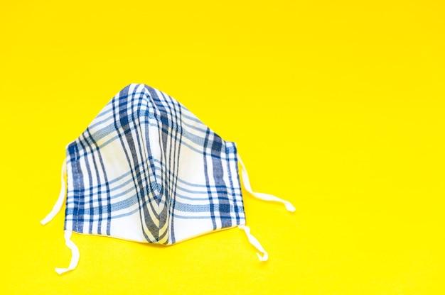Máscara facial de tecido caseiro para proteção contra coronavírus isolado em fundo amarelo