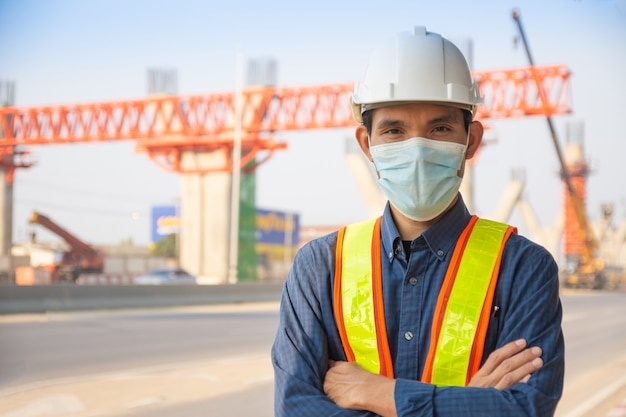 Máscara facial de trabalhador de engenheiro de homem asiático em pé na construção do local, capacete de arquitetura protege o controle do trabalhador