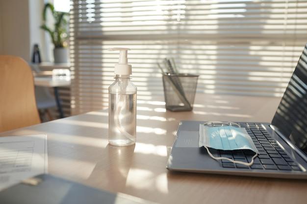 Máscara facial e desinfetante para as mãos na mesa vazia do local de trabalho em um escritório pós-pandêmico iluminado pela luz solar