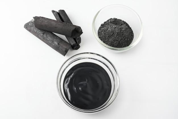 Máscara facial e esfregue pelo pó de carvão ativado no fundo branco