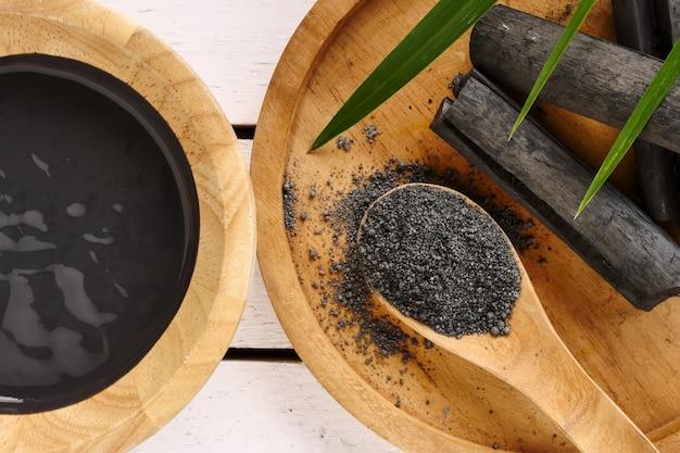 Máscara facial e esfregue por pó de carvão ativado na mesa de madeira