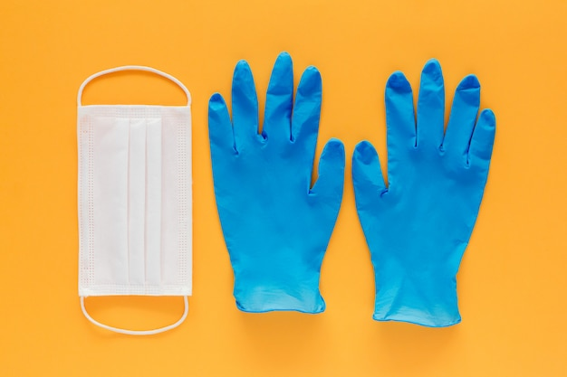 Máscara facial e um par de luvas de látex azuis em um fundo amarelo. conceito de prevenção do coronavírus